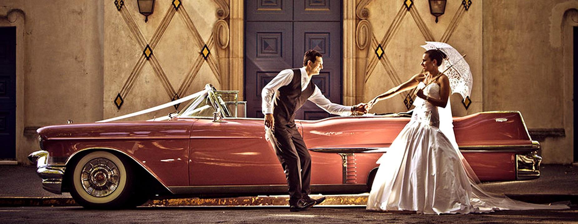 Rosa Cadillac veteranbil som bryllupsbil med brudepar utenfor flott bygning