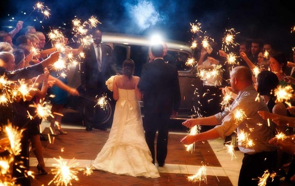 Brudepar på vei inn i en flott gammel bryllupsbil med masse bryllupsgjester rundt