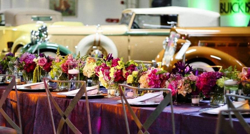 I bakgrunnen for bryllupsfesten står veteranbiler innleid inn til bryllupet.